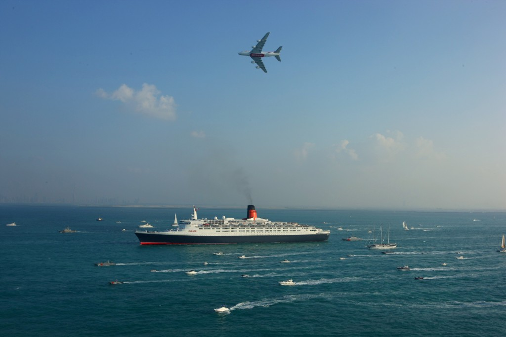 QE2 arrives in Dubai joined by an Emirates A380 Airbus and a flotilla of over 60 local yachts, boats and leisure-craft